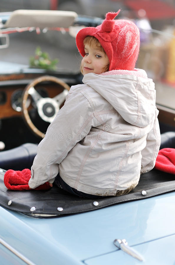 Little girl. Girl sitting on the back of a car royalty free stock images