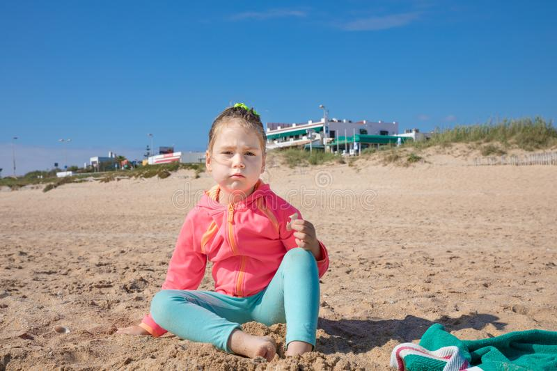 Little girl sitting on the beach looking at with angry expression face stock images