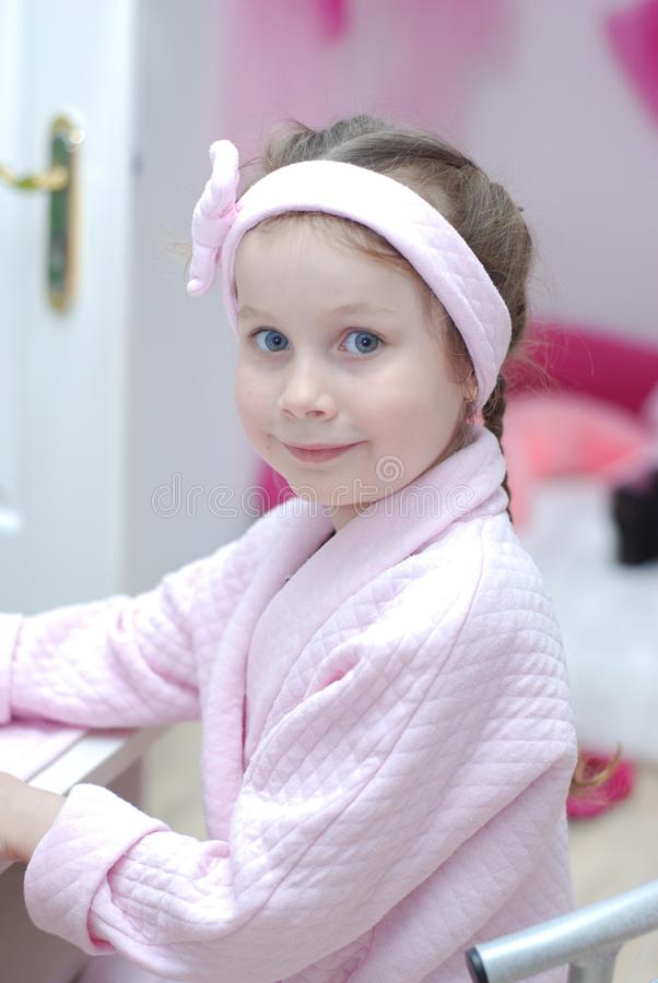 Little Girl is Sitting in the Beauty Salon Chair. Portrait of a Girl in a Pink Dressing Gow, Smiling. Blurred Pink royalty free stock image