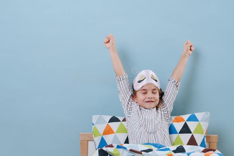 Little girl is sitting in bed in pajamas with lights on, stretching over blue stock photo