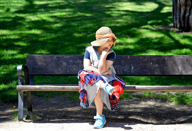 Little girl sitting on the bench in park. stock photos