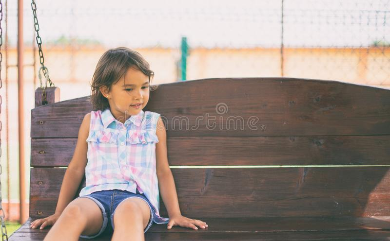 Little girl sitting on bench in the park at the day time royalty free stock photos