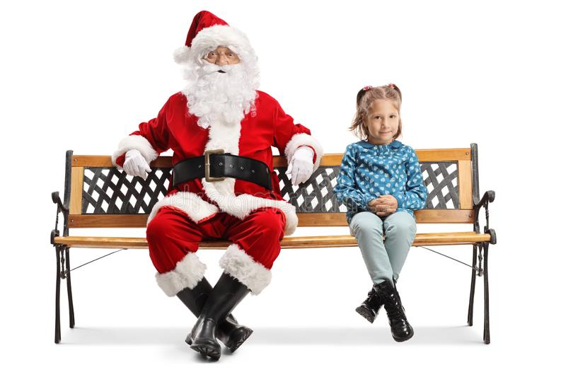Little girl sitting on a bench with Santa Claus. Isolated on white background stock photo