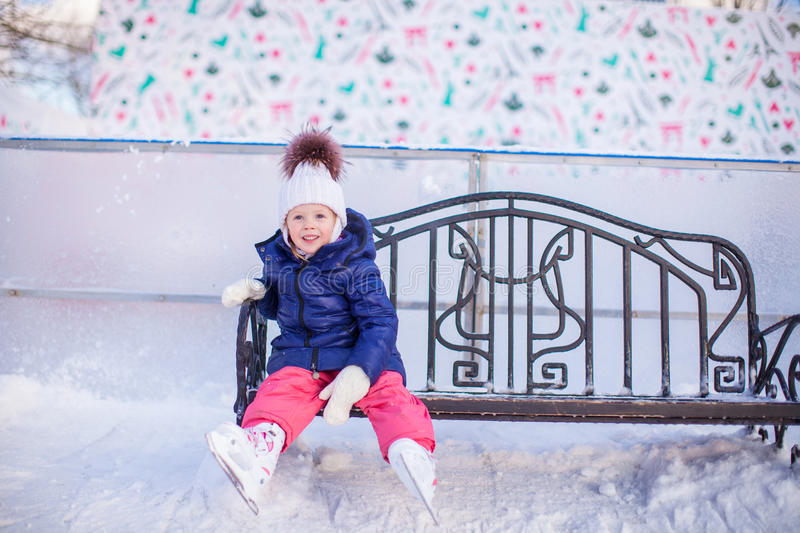 Little girl sitting on a bench in the skating rink. This image has attached release stock photography