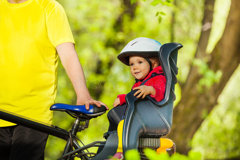 Little girl sitting in bike seat during cycling. Portrait of little girl in bicycle helmet sitting in bike child seat during cycling in sunny forest royalty free stock photo