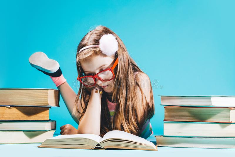 Little girl sitting by the books, studying. stock image