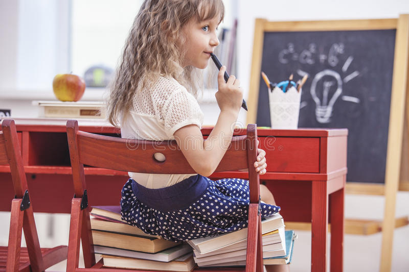 Little girl sitting on the chair and on the books at school in c royalty free stock photos