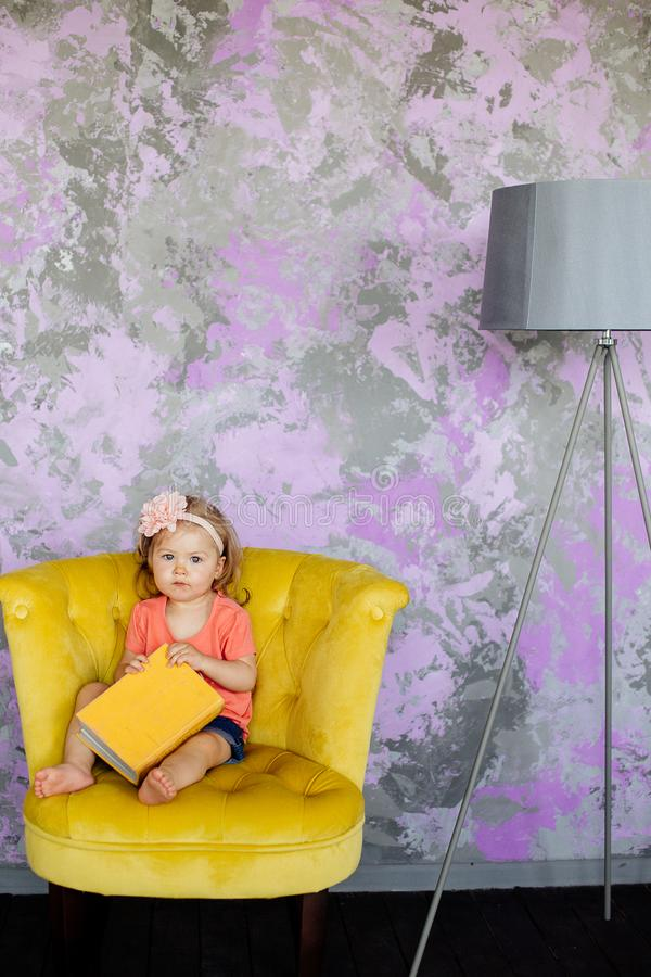 Little girl is sitting in a chair. stock photography
