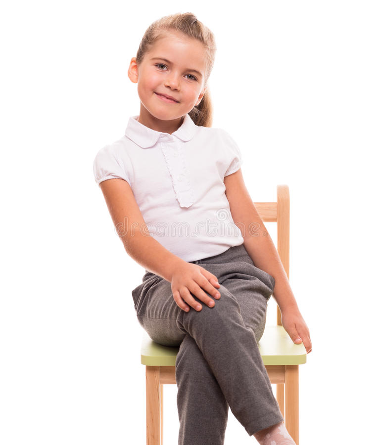 Little Girl Sitting On A Chair And Smiling Stock Photo