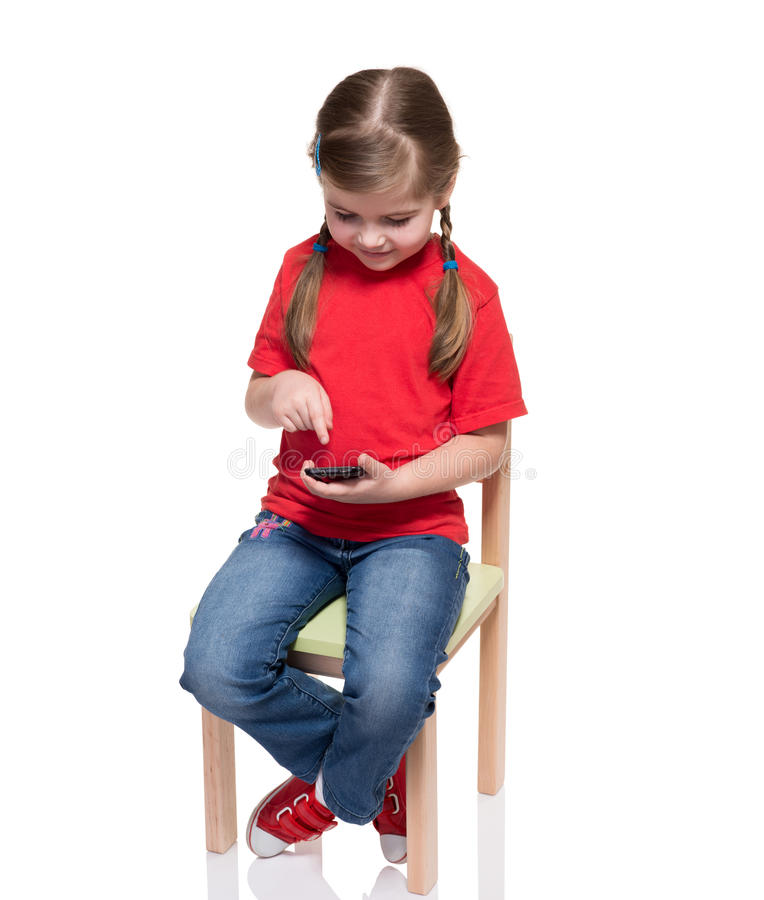 Little Girl Sitting On A Chair And Using Smartphone Stock Photo