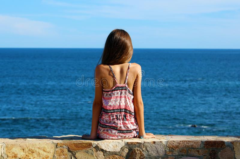 Little girl sitting at cliff at ocean front in Los Cabos Mexico resort cliff sea. Ocean oceano mar stock photography