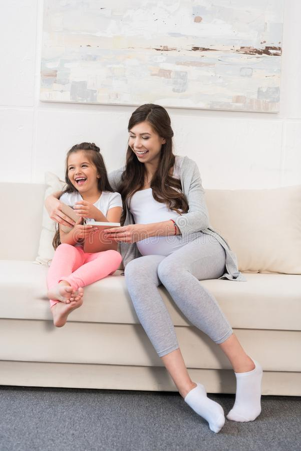 Little girl sitting on couch with mother stock images