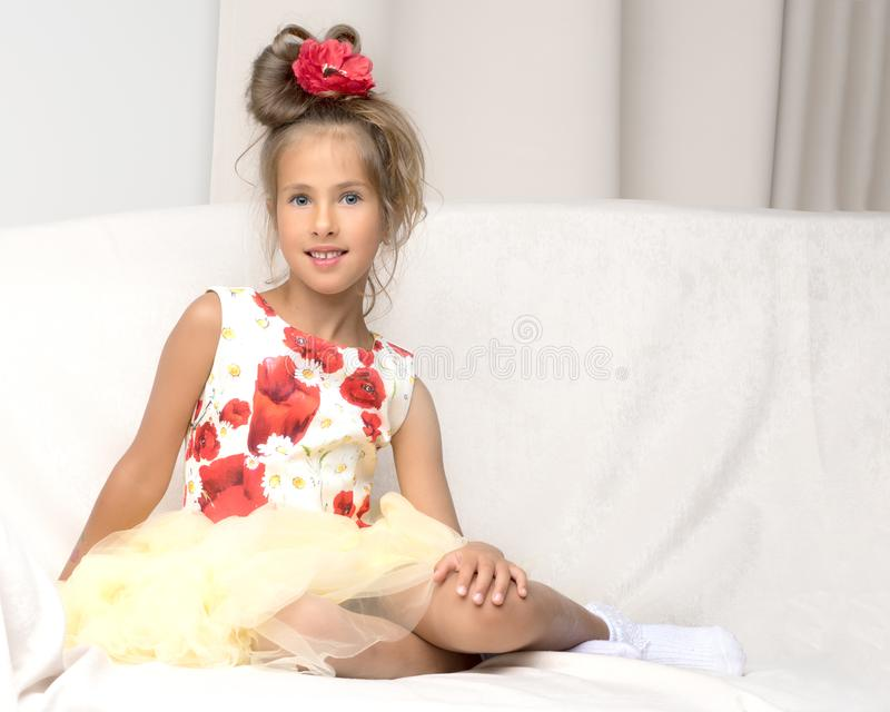 Little girl is sitting on the couch stock photography