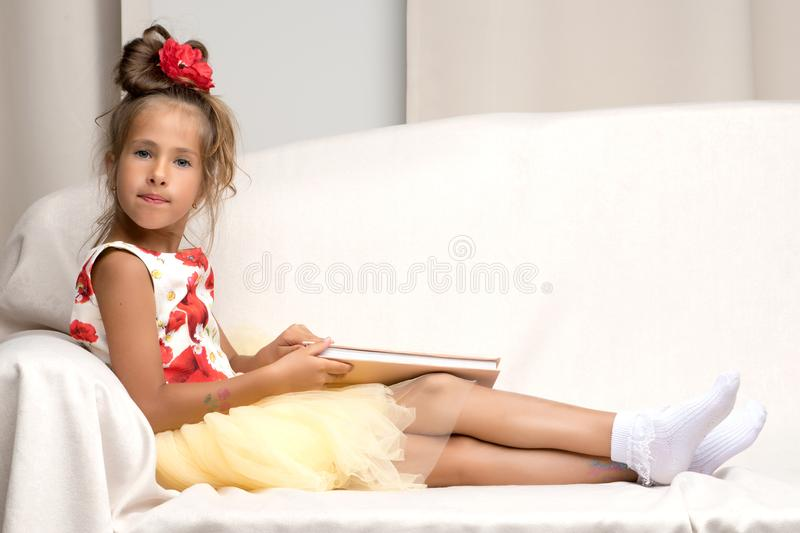 A little girl is sitting on the couch and reading a book. stock image