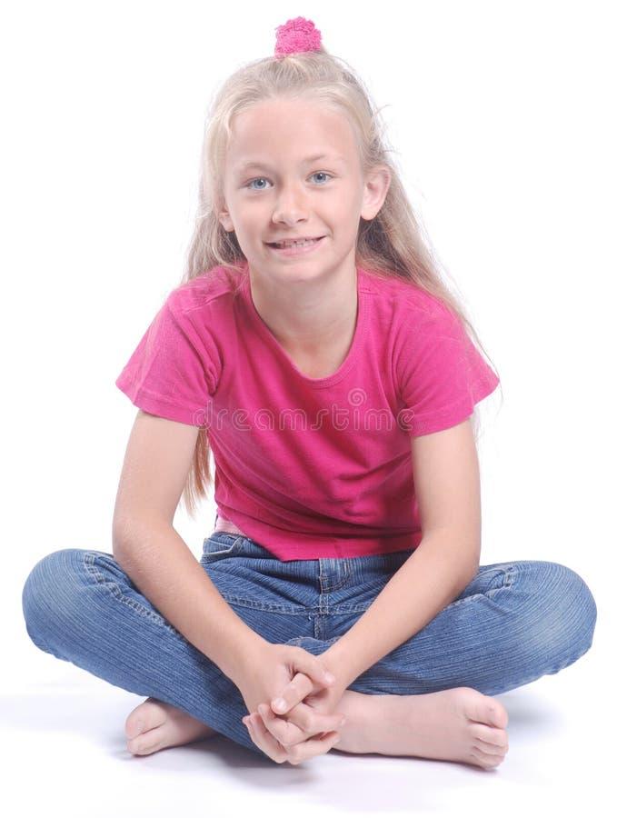 Little girl sitting cross-legged royalty free stock photo