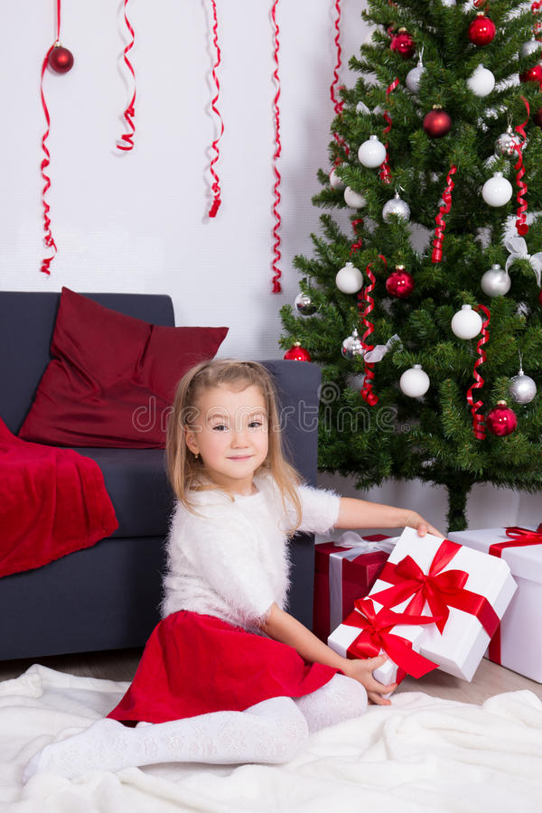 Little girl sitting in decorated living room with Christmas tree stock photo