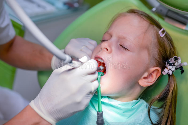 Little girl sitting in the dentists office stock images