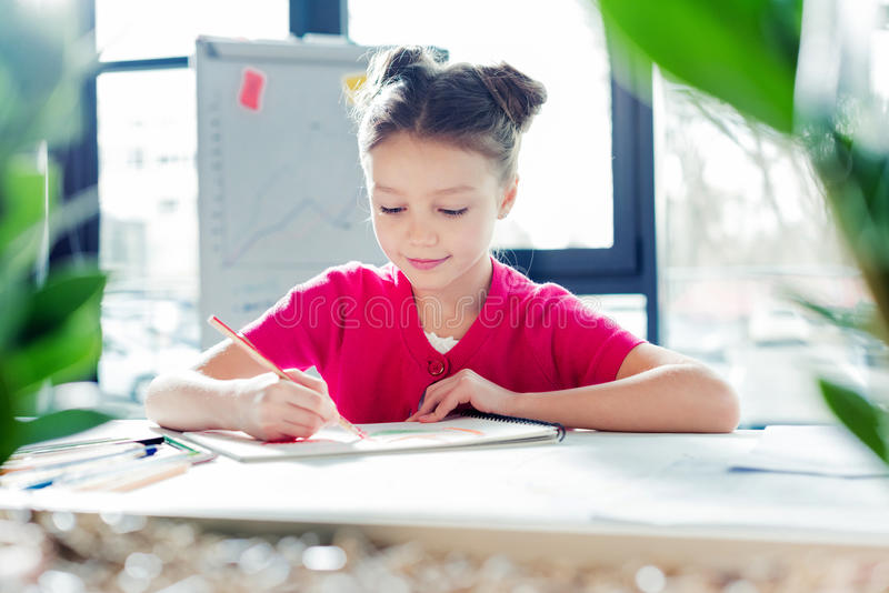 Little girl sitting at desk and drawing in office stock images