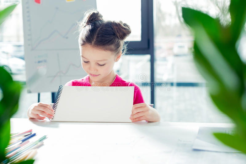 Little girl sitting at desk and holding drawing album in office royalty free stock photography