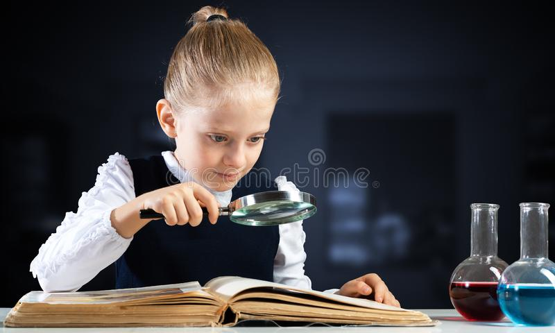 Little girl sitting at desk with magnifier royalty free stock images