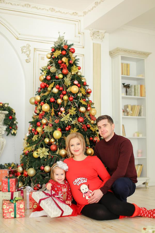 Little girl sitting with father and pregnant mother near Christmas tree and keeping gifts. royalty free stock images