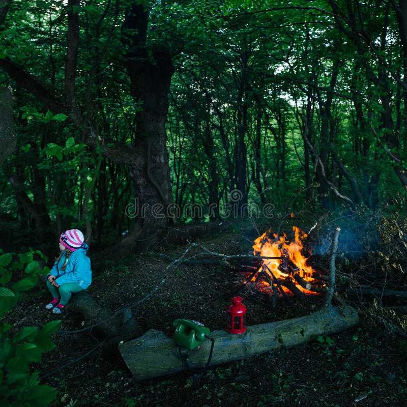 A little girl sitting by the fire in the forest. royalty free stock image
