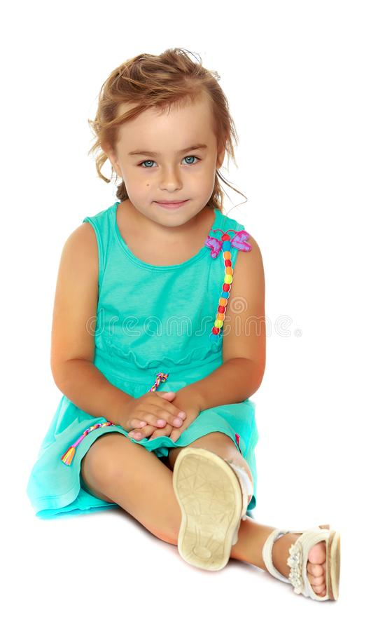 Little girl is sitting on the floor. stock image