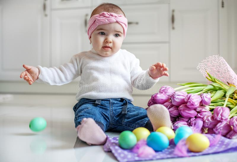 Little girl sitting on the floor Easter eggs. Concept Happy Eas stock photography