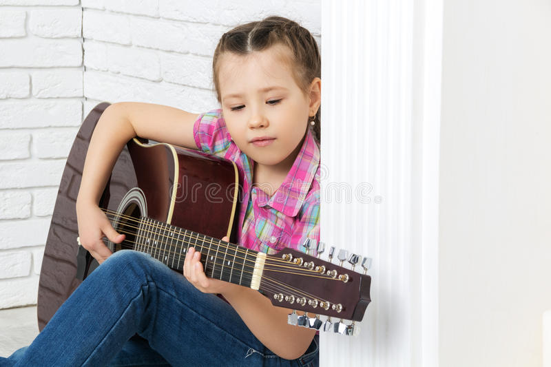Little girl sitting on the floor and playing guitar royalty free stock photo