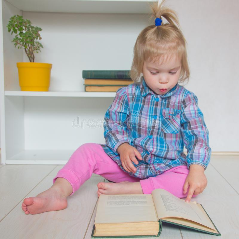 A little girl is sitting on the floor and reading a book. The ch royalty free stock images