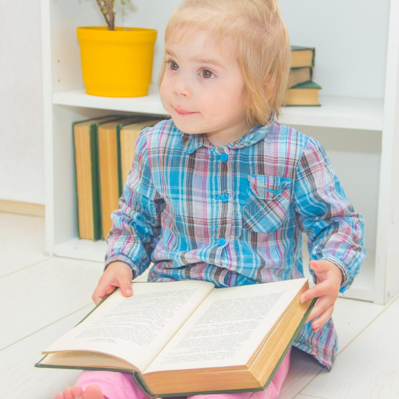 A little girl is sitting on the floor and reading a book. The ch stock photos