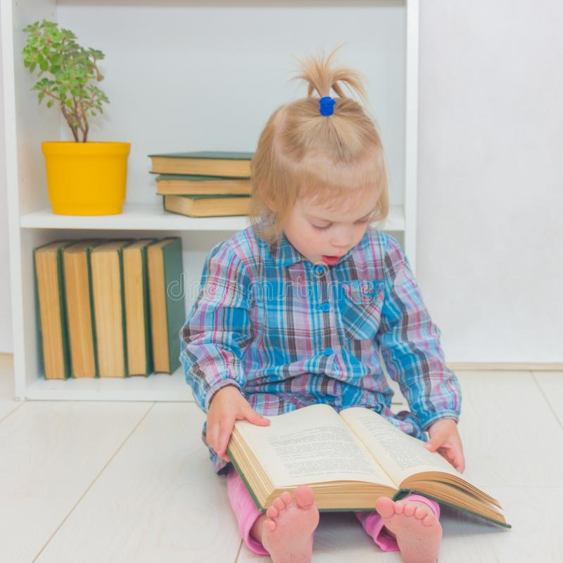 A little girl is sitting on the floor and reading a book. The ch stock photo