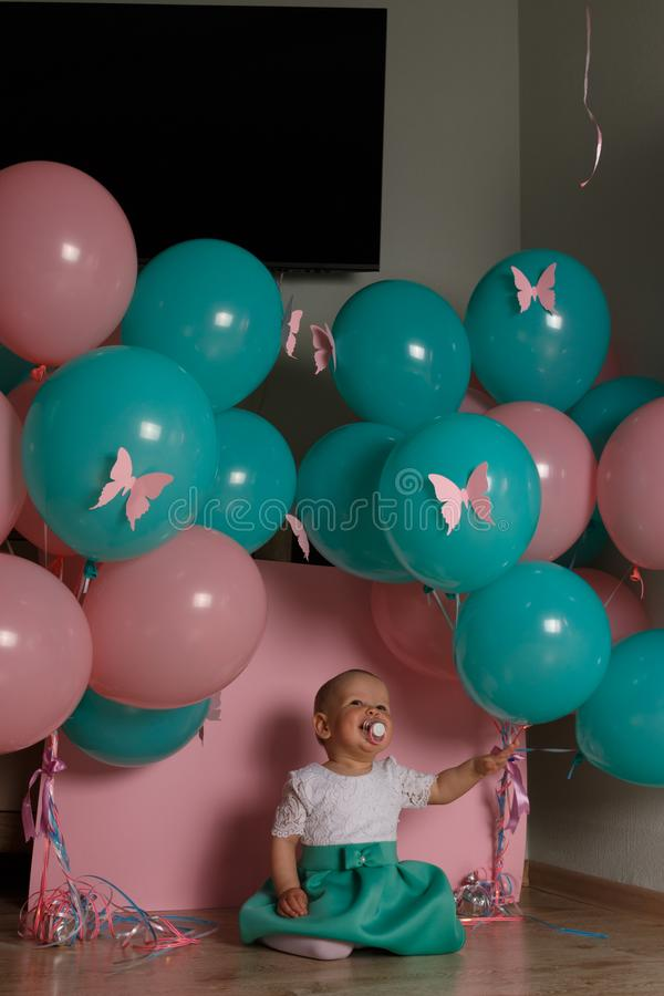 little girl sitting on the floor in the room next to the balloons, first birthday, celebrate. one year old blue and pink balls wit stock photo