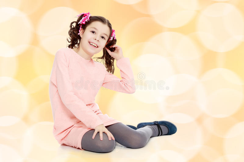 Little girl sitting on the floor and straightens hair. royalty free stock photo