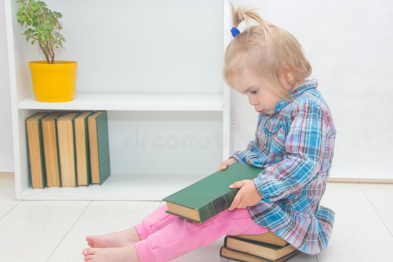 Little girl is sitting on the floor and thumbs a book. The child royalty free stock photo