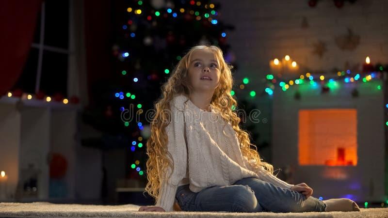 Little girl sitting on floor, waiting Santa on Christmas eve, magical moment. Stock photo stock images