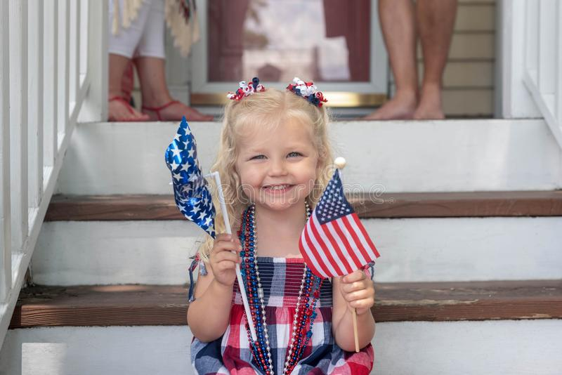 Little girl sitting on front steps on Fourth of July. Cute young girl holding American flag sitting on front porch on Fourth of July stock image
