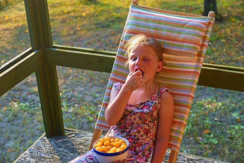 The little girl is sitting on a garden deckchair on a verandah. Small girl is eating cheese flavoured snacks in the royalty free stock photography
