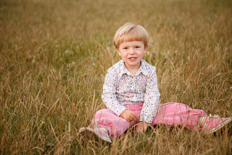Little girl sitting in the grass royalty free stock photography