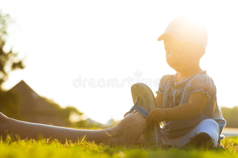 Little girl sitting on the grass and putting flip flips on mother leg on sunny day. Little baby in hat and dress is helping mother to put on shoes royalty free stock images