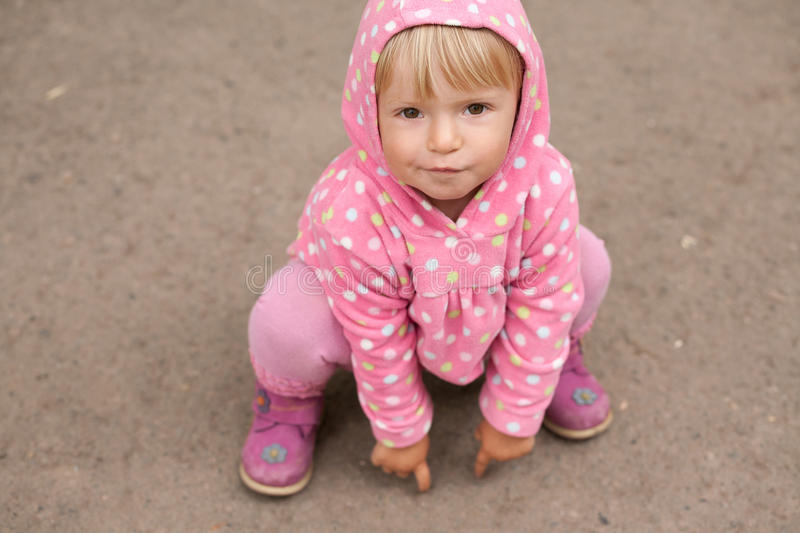 Little girl sitting on the ground stock image