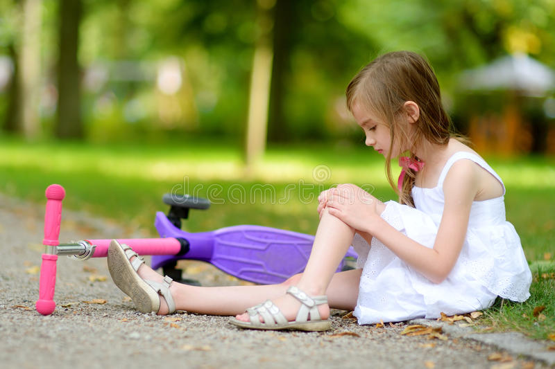 Little girl sitting on the ground after she fell while riding her scooter stock photography