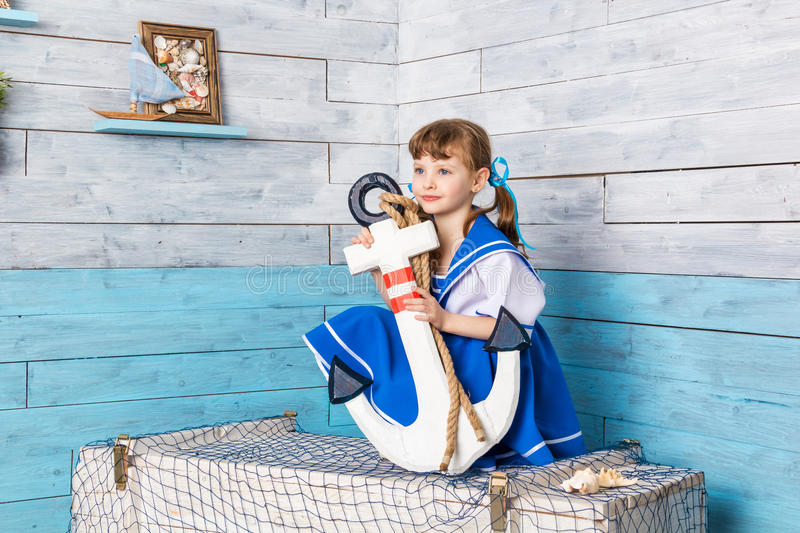 Little girl sitting and holding an anchor royalty free stock images