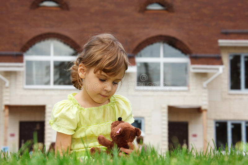 Little girl sitting on lawn in front of new home stock photo