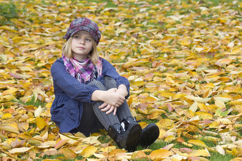 Little girl sitting on leaves royalty free stock photo