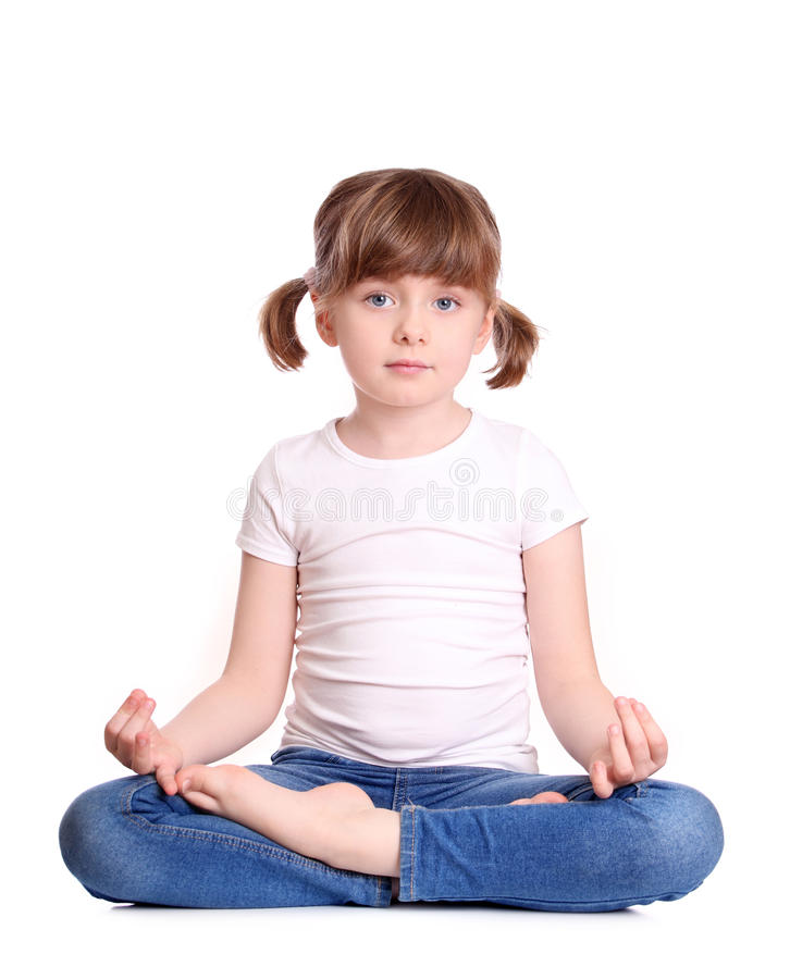 Little girl sitting lotus position. Isolated on white background royalty free stock photo