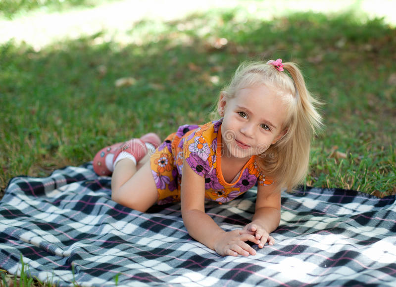 Little girl sitting in the park royalty free stock photo