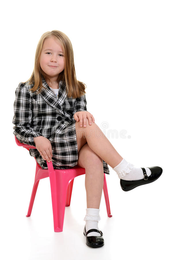 Little girl sitting in pink chair stock photography