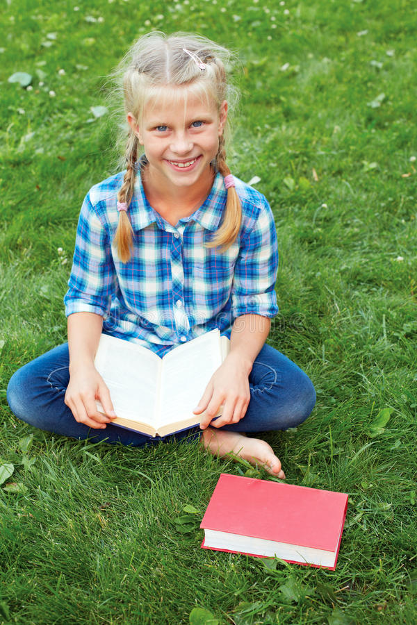 Little girl is sitting reading on the grass. stock image
