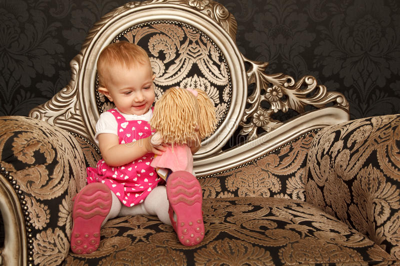 Download Little Girl Sitting On Retro Armchair With Doll Stock Photo - Image: 12729364
